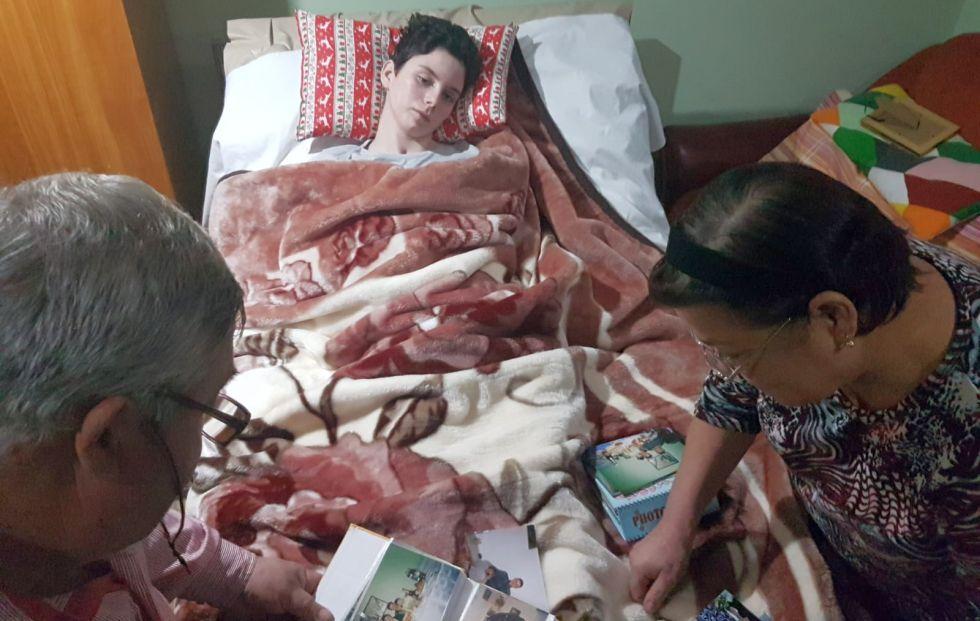 O scenă aproape ca un tablou. Ana, imobilizată în pat, în timp ce părinții ei de suflet, Fănel și Maricica, privesc fotografiile copilărei fetei pe care n-au abandonat-o
