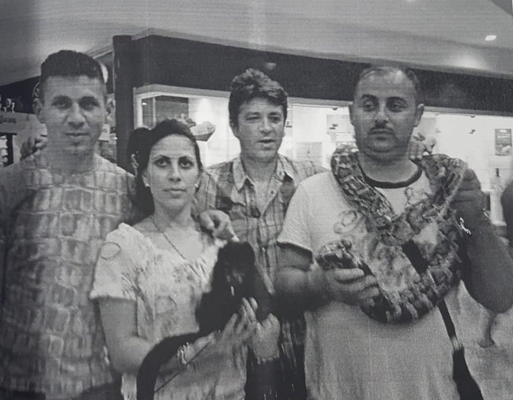 Filip Sărdaru (first person on the right), the head of one of the trafficking cland, had his picture taken in Mexico, with a snake around his neck