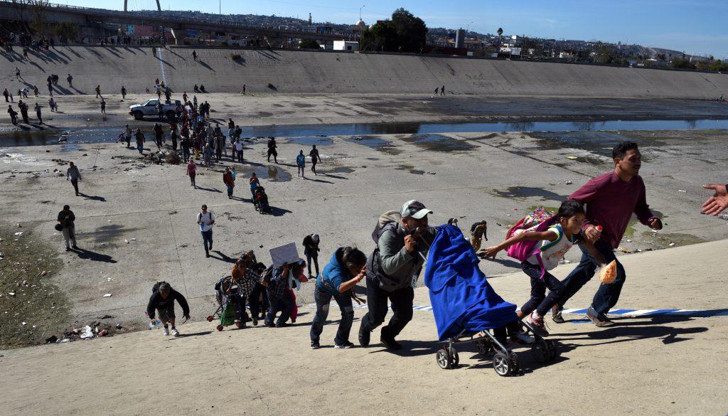 Migranți se grăbesc să traverseze albia secată a râului Tijuana în încercarea de a escalada gardul spre Statele Unite. Foto: Northfoto