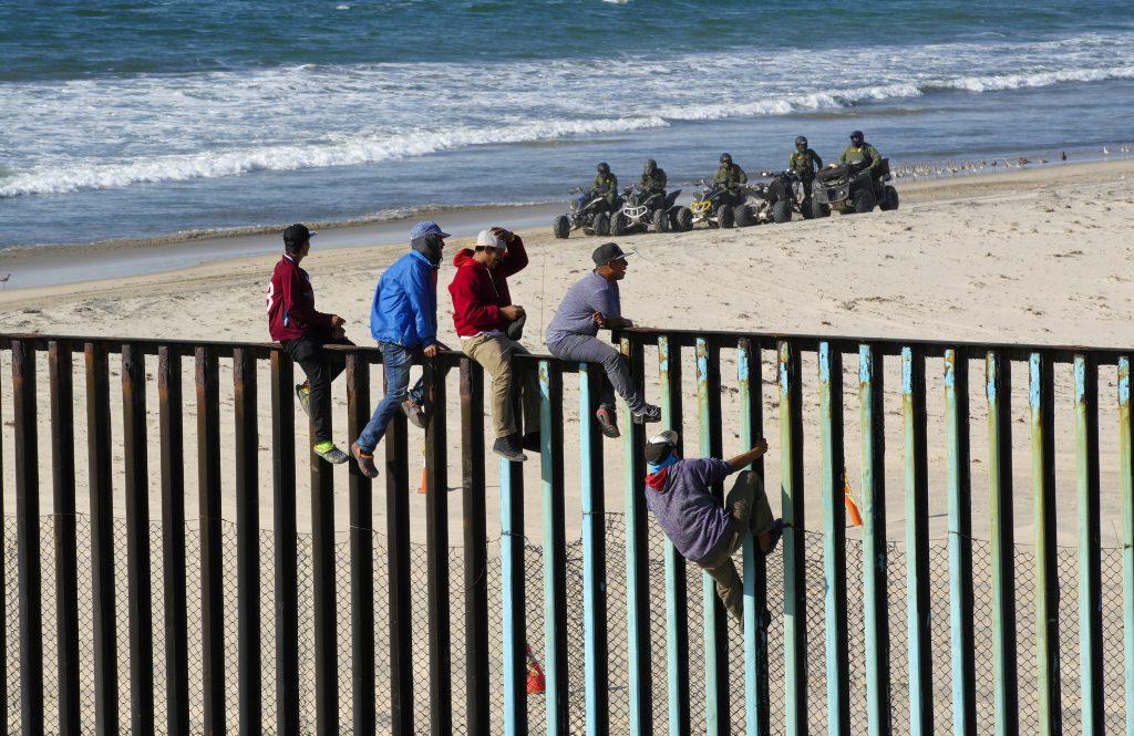 Migranți din America Centrală escaladează gardul care separă Mexic de SUA sub privirile poliției de frontieră Americană. Persoanele care apar în aceste fotografii nu au legătură cu personajele din articolul publicat de Libertatea. Foto: Hepta